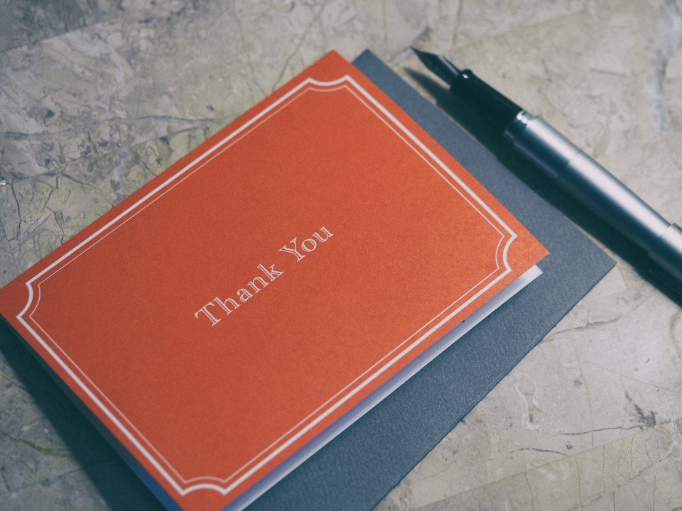 "Red card with the words ""thank you"" on it next to a fountain pen."