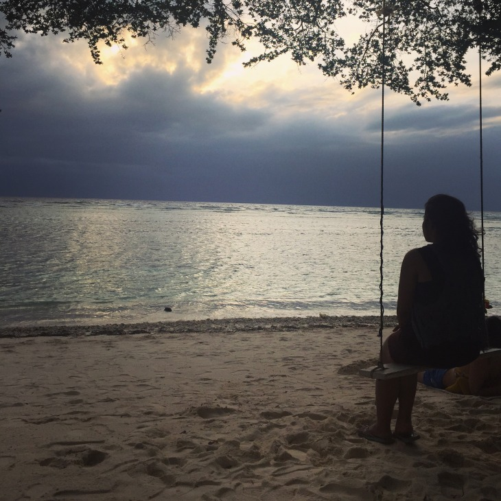 The author, on a swing, gazing at a large body of water, her back to the viewer, in Indonesia.