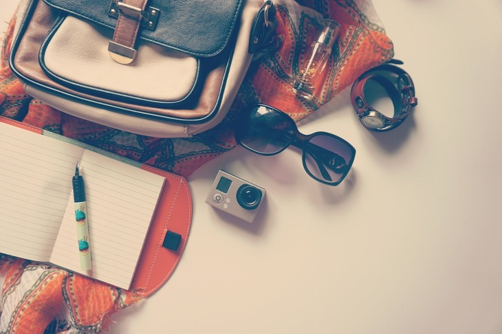Travel bag with contents spilled out: sunglasses, notebook and pen, camera, a watch, and perfume.
