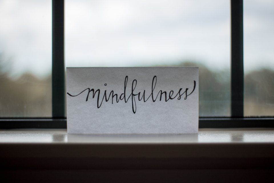 "A piece of paper with the word ""mindfulness"" on it leaning against a window"