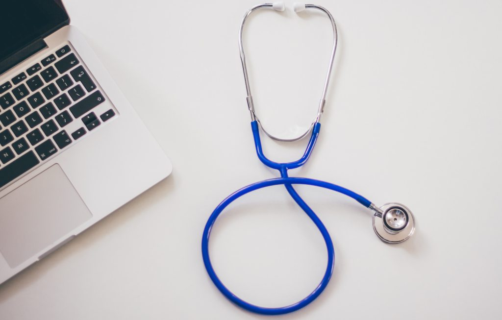 Stethoscope next to a laptop on a white surface.