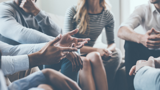 Stock photo of people in a group (faces not in frame), gesturing with their hands, having a conversation