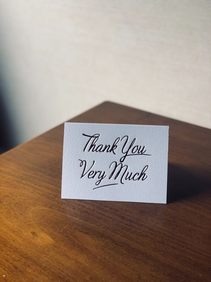 "Card on wooden table reads ""Thank You Very Much"""