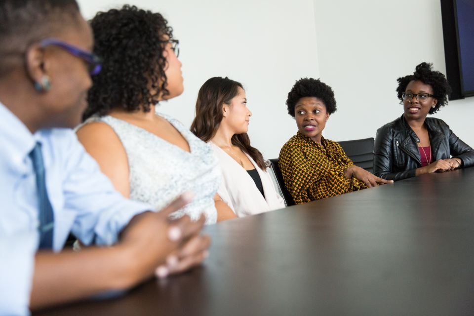 five women of colour sitting around boardroom table, talking