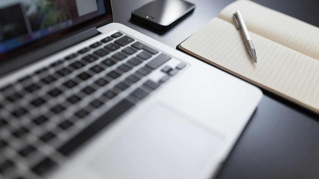 Stock image of open laptop with phone, notebook, and pen