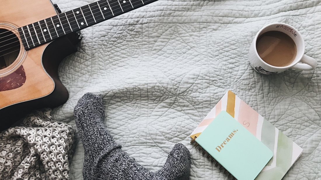 """Mug of coffee on a bedspread, with a guitar, a couple of notebooks (the top one has """"Dreams"""" written on the cover), and a couple of feet in socks poking from bottom of image."""