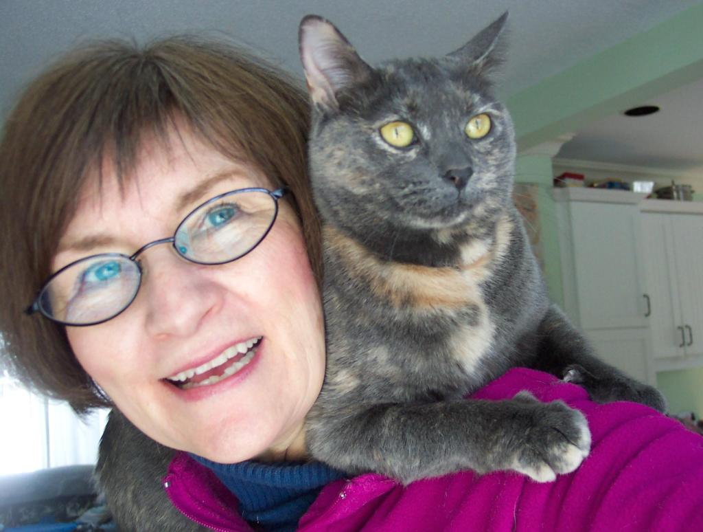 Photo of Marie-Lynn Hammond with grey cat perched on her shoulders.