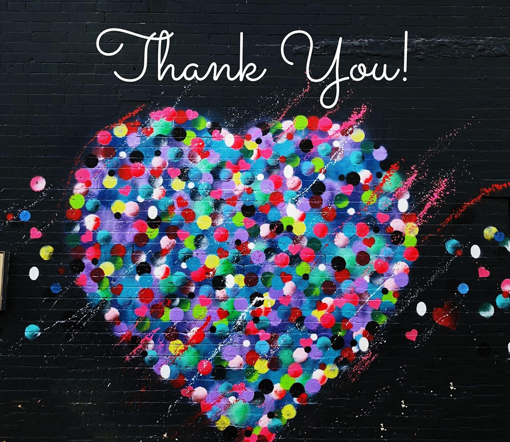 "The words ""Thank you!"" in cursive script on a black background above a huge heart made up of colourful confetti."