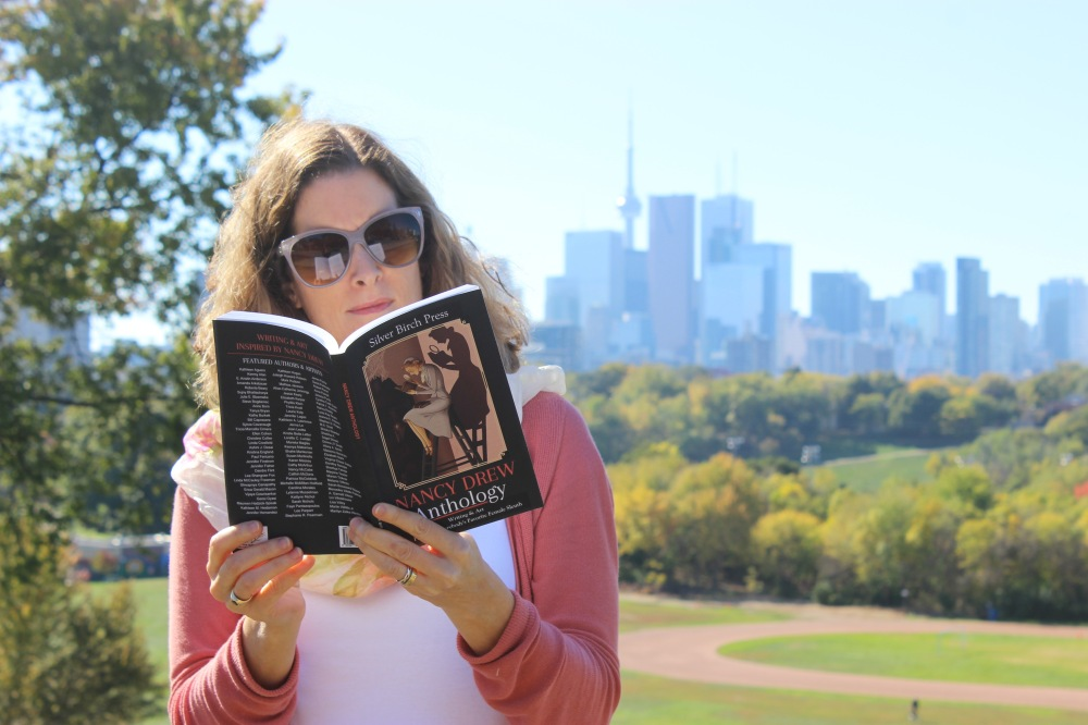Photo of Lee Parpart reading a book with the Toronto skyline in the background.