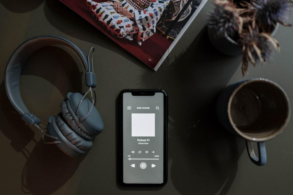 Photo of a smartphone with a podcast playing, with a set of headphones on the left and a mug of coffee on the right.